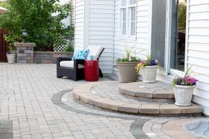 Rounded Steps to Back Door of Luxury Home Stone Patio with Comfortable Wicker Furniture and Flower Pots